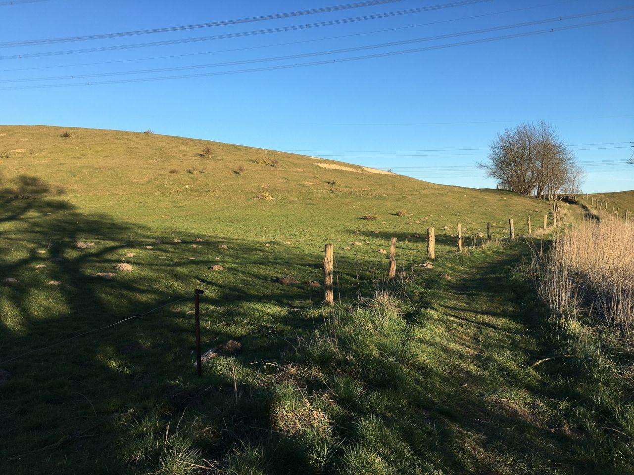 Landschaftsbild mit Himmel und viel grün, ein Weg der an einem Weidezaun entlang eines Hügels führt