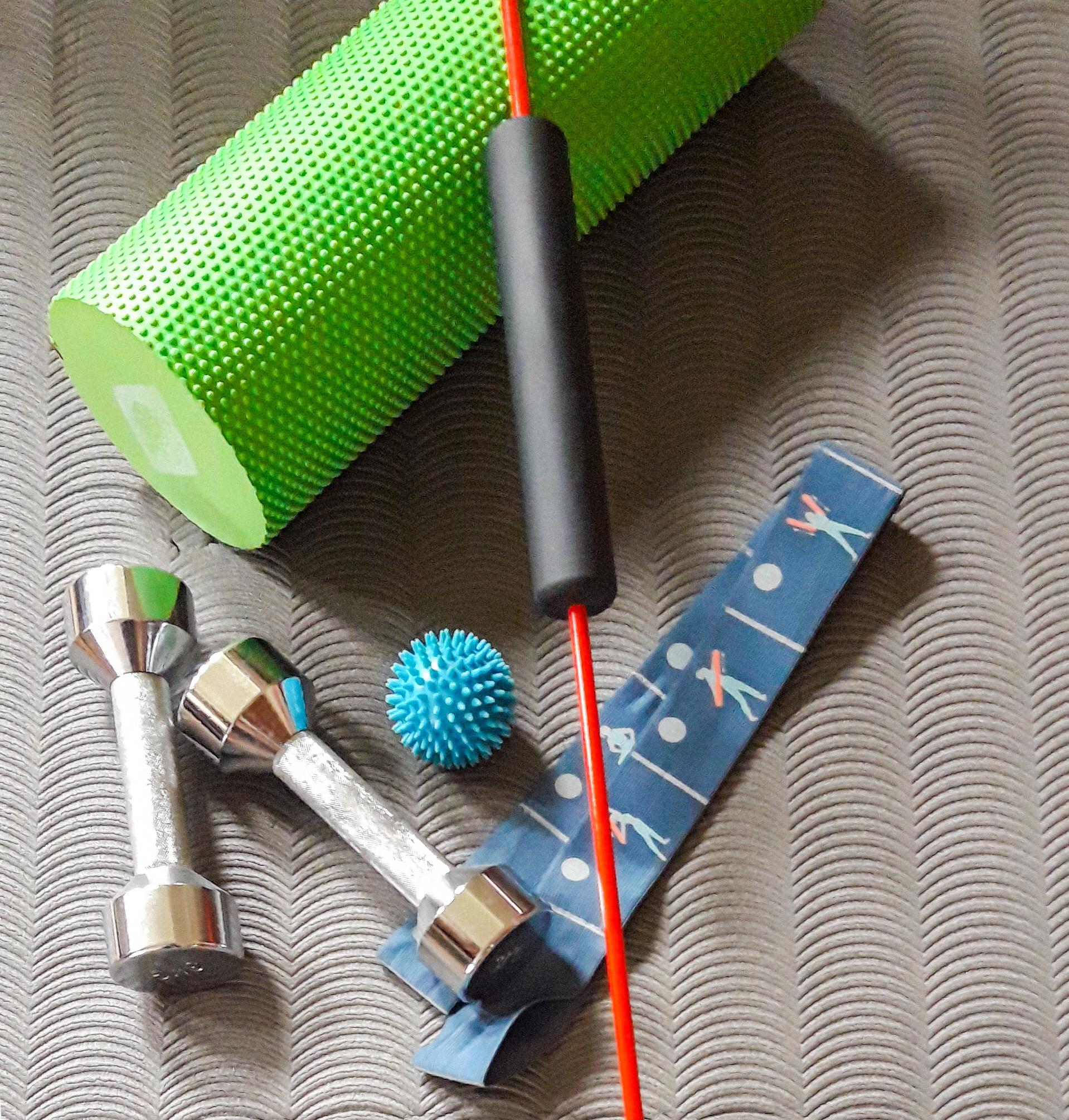 Diverse Fitnessgegenstände wie Hanteln, Schwingstab, Faszienrolle, Stretchbänder und Igelball