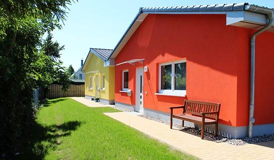 Zwei einstöckige Beispielhäuser des Wohnparks in freundlichen Farben, grüner Natur drumherum und einer Bank vor einem der Häuser